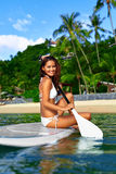 Fritidsaktivitet Kvinnan står paddla som upp surfar fritids- Arkivfoto