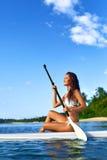 Fritidsaktivitet Kvinnan står paddla som upp surfar fritids- Royaltyfri Fotografi
