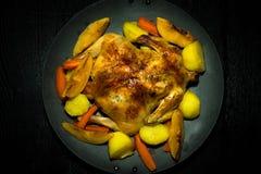 Frito chiken con las verduras en una cacerola en una tabla de madera negra T Imagen de archivo libre de regalías