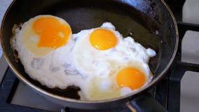 Frito tres huevos fritos en una cacerola almacen de metraje de vídeo