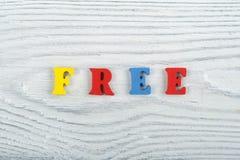 FRITT ord på träbakgrund som komponeras från träbokstäver för färgrikt abc-alfabetkvarter, kopieringsutrymme för annonstext royaltyfri fotografi