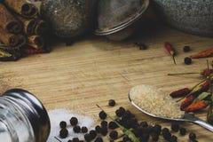 Fritt utrymme för text på träbakgrund av skärbrädan med trätextur och spridda kryddor på den Sikt på utan laga kraft trä arkivbild