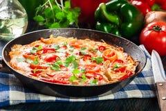 Frittata сделанный из яичек, chorizo сосиски, красного перца, зеленого перца, томатов, сыра и chili в лотке на деревянном столе Стоковая Фотография RF