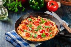 Frittata сделанный из яичек, chorizo сосиски, красного перца, зеленого перца, томатов, сыра и chili в лотке на деревянном столе Стоковые Фото