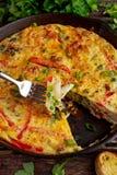 Frittata сделанный из яичек, картошка, бекон, паприка, петрушка, зеленые горохи, лук, сыр в железном лотке таблица поля глубины о Стоковое фото RF