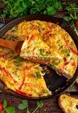 Frittata сделанный из яичек, картошка, бекон, паприка, петрушка, зеленые горохи, лук, сыр в железном лотке таблица поля глубины о Стоковое Изображение