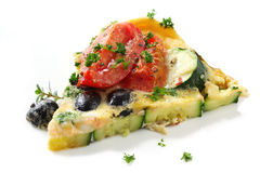 Frittata. Wedge of vegetable frittata. Italian style omelette, with roma tomatoes, zucchini (courgette) and black olives. Garnished with parsley and thyme royalty free stock image