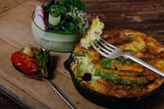 Frittata with asparagus. Ingridiens onion, tomato, herbs royalty free stock image