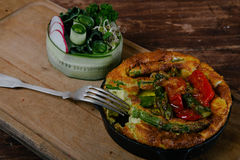 Frittata with asparagus. Ingridiens onion, tomato, herbs stock image