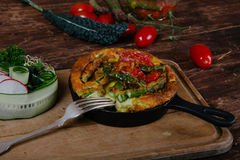 Frittata with asparagus. Ingridiens onion, tomato, herbs Royalty Free Stock Photo