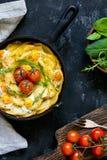 Frittata avec des pommes de terre, des épinards, des tomates et le fromage images libres de droits