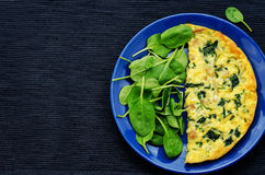Frittata with chicken and spinach and fresh spinach Stock Image