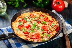 Frittata fait d'oeufs, chorizo de saucisse, poivron rouge, poivron vert, tomates, fromage et piment dans une casserole sur la tab photos libres de droits