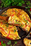 Frittata feito dos ovos, batata, bacon, paprika, salsa, ervilhas verdes, cebola, queijo na bandeja do ferro Na tabela de madeira Imagem de Stock