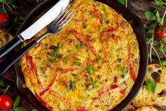 Frittata feito dos ovos, batata, bacon, paprika, salsa, ervilhas verdes, cebola, queijo na bandeja do ferro Na tabela de madeira Imagem de Stock Royalty Free
