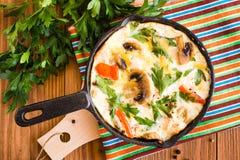 Frittata feito dos ovos, dos tomates, dos cogumelos, da galinha e do queijo em uma frigideira e em uma salsa fresca em uma tabela foto de stock royalty free