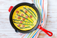 Frittata with fresh asparagus and cherry tomatoes. Top view stock photography