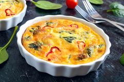 Frittata with fresh vegetables and spinach. Italian omelet in ceramic forms stock image