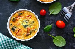 Frittata with fresh vegetables and spinach. Italian omelet in ceramic forms on a black background. stock photography