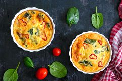 Frittata with fresh vegetables and spinach. Italian omelet in ceramic forms on a black background. royalty free stock photos