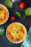 Frittata with fresh vegetables and spinach. Italian omelet in ceramic forms on a black background. stock photos