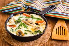 Frittata gemacht von den Eiern, vom Huhn, von den Pilzen, von den Zwiebeln und von den Tomaten Stockbilder