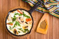 Frittata gemacht von den Eiern, vom Huhn, von den Pilzen, von den Zwiebeln und von den Tomaten Stockfotos