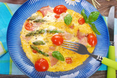 Frittata with green asparagus,ham and cherry tomato Royalty Free Stock Photo