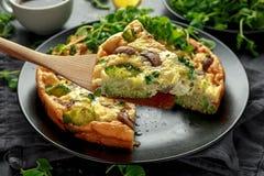 Frittata hecho en casa con las setas, el bróculi, el queso feta, los guisantes verdes y el tocino en la placa negra Fotos de archivo