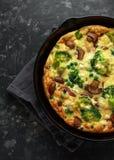 Frittata hecho en casa con las setas, el bróculi, el queso feta, los guisantes verdes y el tocino en la sartén del arrabio  Imagen de archivo