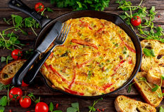Frittata made of eggs, potato, bacon, paprika, parsley, green peas, onion, cheese in iron pan. on wooden table. Royalty Free Stock Image