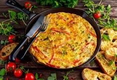 Frittata made of eggs, potato, bacon, paprika, parsley, green peas ...