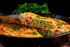Frittata made of eggs, potato, bacon, paprika, parsley, green peas, onion, cheese in iron pan. on wooden table. Royalty Free Stock Photography