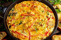 Frittata made of eggs, potato, bacon, paprika, parsley, green peas, onion, cheese in iron pan. on wooden table. Frittata made of eggs, potato, bacon, paprika stock images