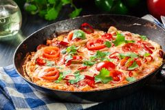 Frittata made of eggs, sausage chorizo, red pepper, green pepper, tomatoes, cheese and chili in a pan on wooden table Royalty Free Stock Image