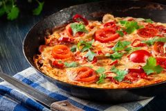 Frittata made of eggs, sausage chorizo, red pepper, green pepper, tomatoes, cheese and chili in a pan on wooden table Royalty Free Stock Photography