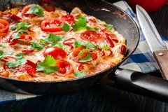 Frittata made of eggs, sausage chorizo, red pepper, green pepper, tomatoes, cheese and chili in a pan on wooden table Stock Photo