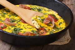 Frittata met tomaat, ham en kruiden in de pan met een spatel Royalty-vrije Stock Foto