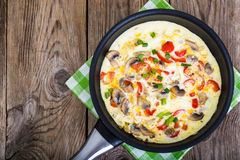 Frittata with mushrooms and peppers in frying pan Stock Photo