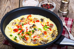 Frittata with mushrooms and peppers in frying pan Royalty Free Stock Photography