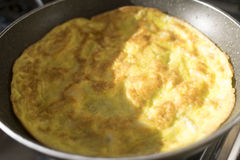 Frittata in pan illumined for half from sun rays Stock Images