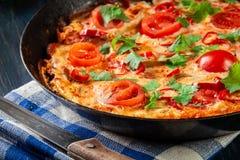Frittata robić jajka, kiełbasiany chorizo, czerwony pieprz, zielony pieprz, pomidory, ser i chili w niecce, na drewnianym stole Obraz Stock