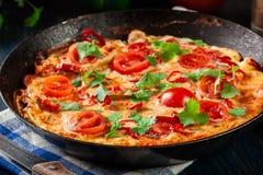 Frittata robić jajka, kiełbasiany chorizo, czerwony pieprz, zielony pieprz, pomidory, ser i chili w niecce, na drewnianym stole Zdjęcie Stock