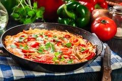 Frittata robić jajka, kiełbasiany chorizo, czerwony pieprz, zielony pieprz, pomidory, ser i chili w niecce, na drewnianym stole Zdjęcia Royalty Free