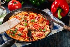 Frittata robić jajka, kiełbasiany chorizo, czerwony pieprz, zielony pieprz, pomidory, ser i chili w niecce, na drewnianym stole Fotografia Stock