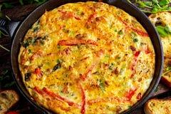 Frittata som göras av ägg, potatis, bacon, paprika, persilja, gröna ärtor, lök, ost i järnpanna trägrund tabell för djupfält arkivbilder