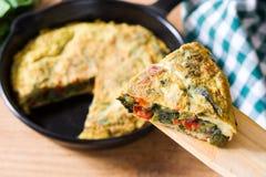 Frittata van eieren en groenten in een ijzerpan wordt gemaakt, op hout dat Stock Foto's