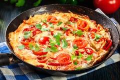 Frittata van eieren, worstchorizo, Spaanse peper, groene paprika, tomaten, kaas en Spaanse peper in een pan op houten lijst wordt Royalty-vrije Stock Afbeeldingen