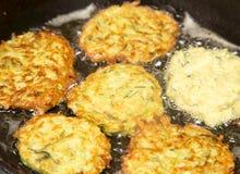 Fritters είναι τηγανισμένα στο πετρέλαιο σε ένα τηγανίζοντας τηγάνι Στοκ Εικόνα