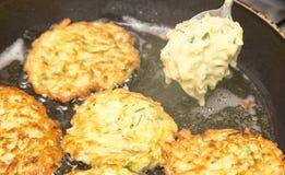 Fritters είναι τηγανισμένα στο πετρέλαιο σε ένα τηγανίζοντας τηγάνι Στοκ Εικόνες